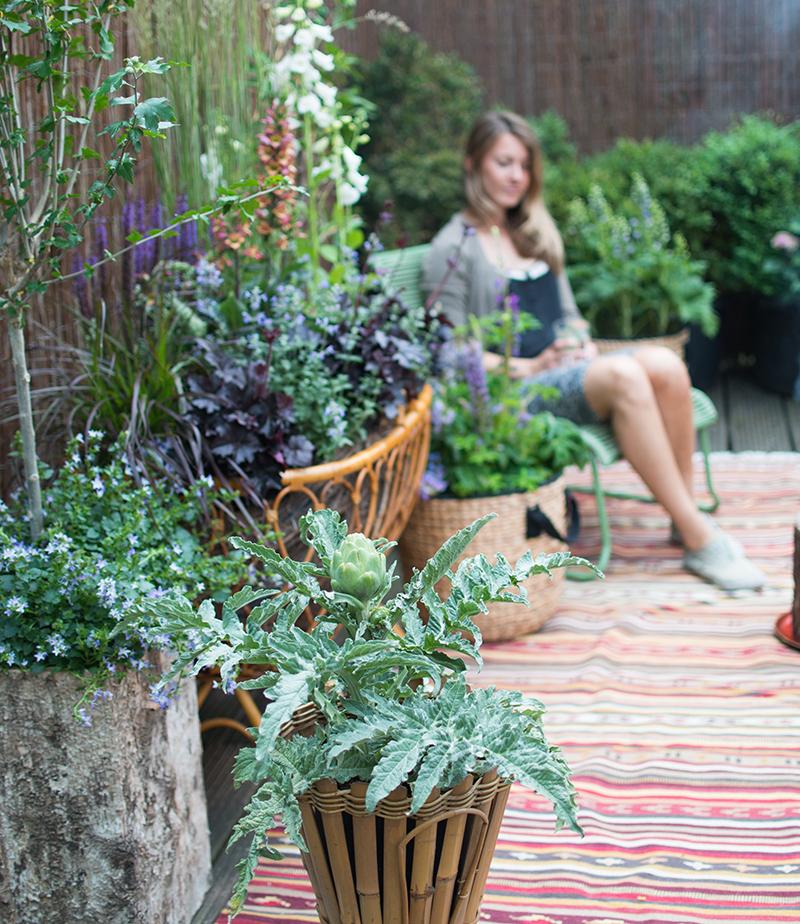 Inredning med krukor matta och sittplats på balkong