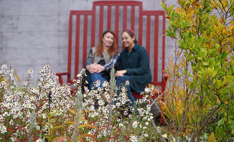 Lena Ljungquist och Karin Elmberg sitter på en röd bänk