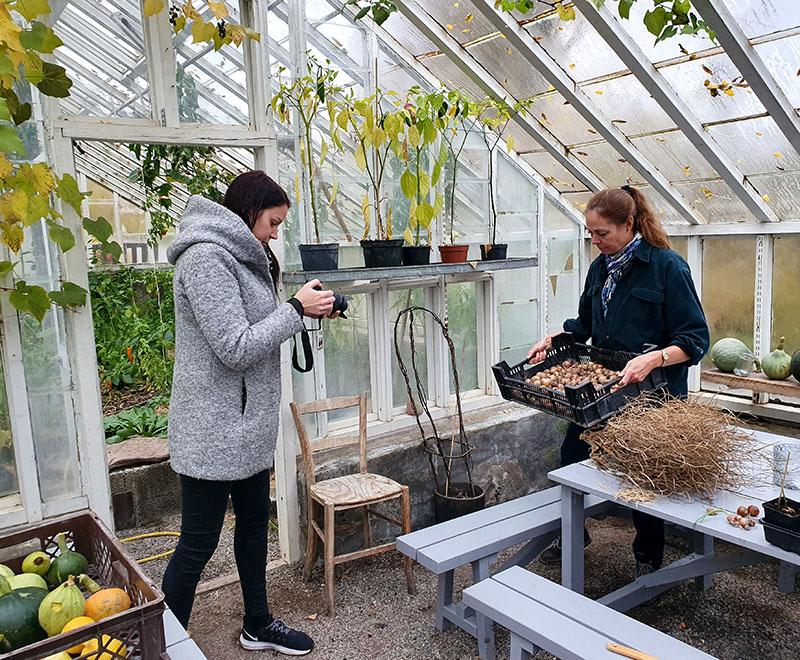 Linda Sandström fotograferar Karin Elmberg i växthuset