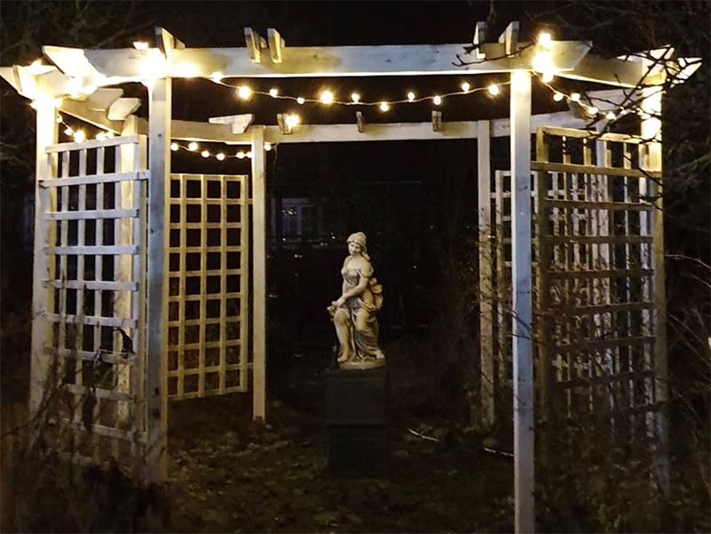 ljusslingor i pergolan lyser upp i mörkret