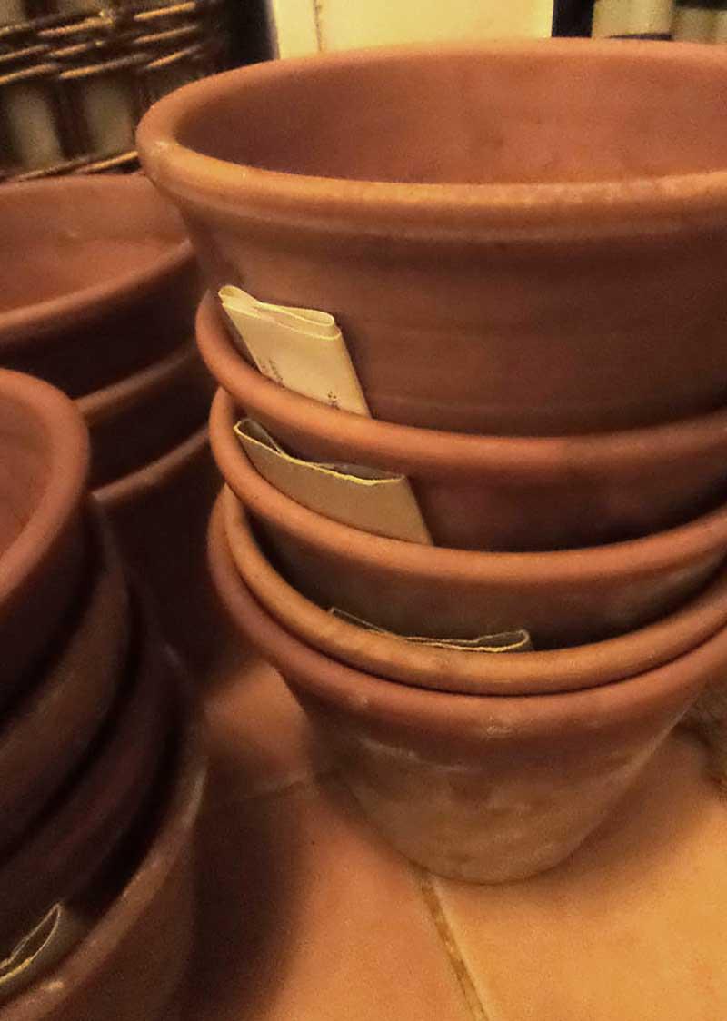 Lerkrukor och terrakottakrukor staplade med papp emellan