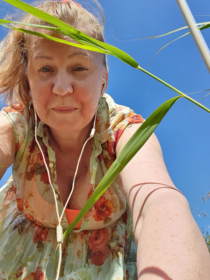 Lena fotograferar växter i diket