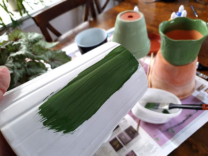 Vit ytterkruka målas i grön mineralfärg