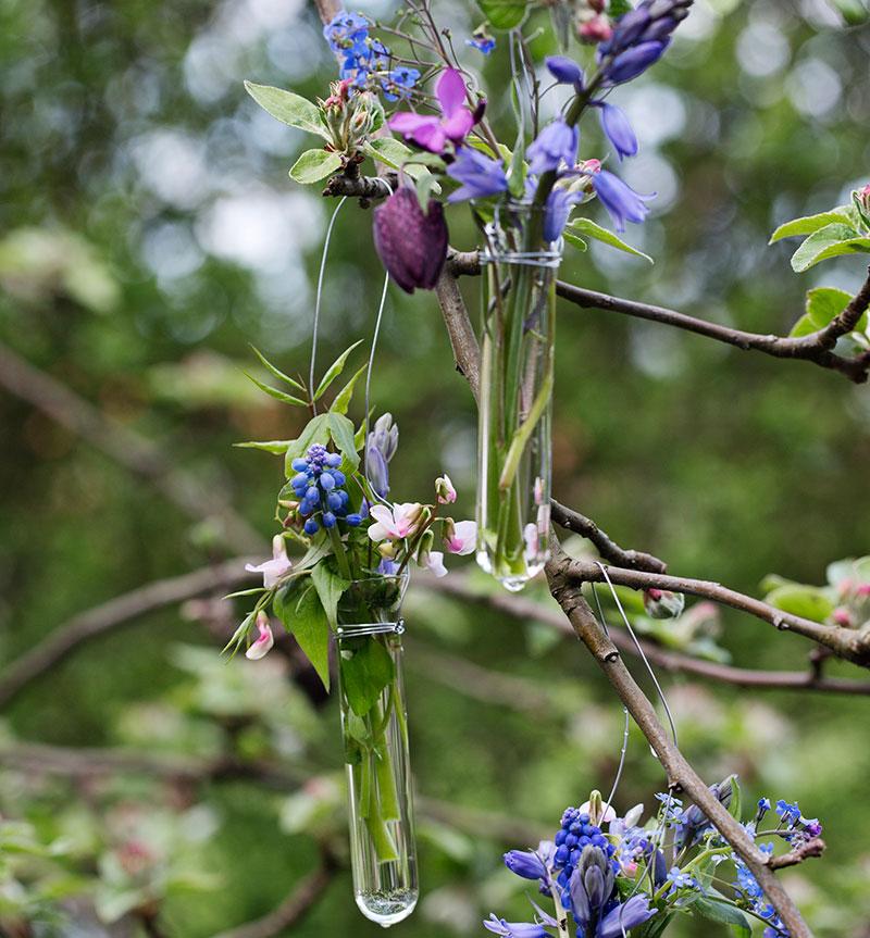 småvaser med vårblommor i träd