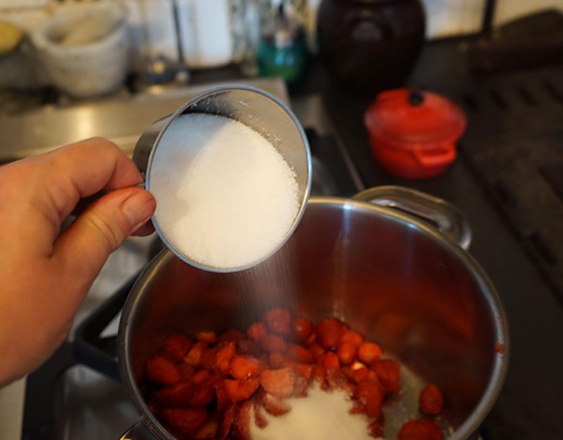 Socker hälls över jordgubbar i grytan