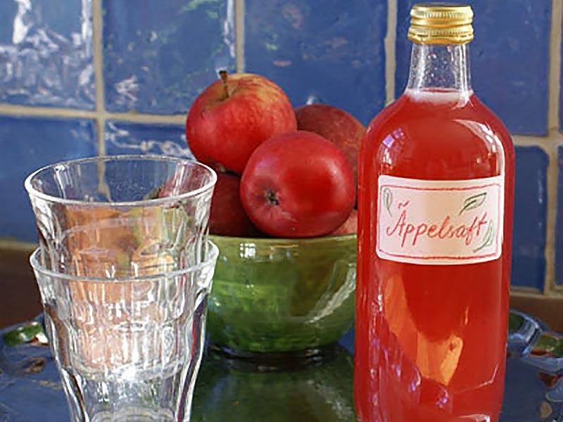 Kallrörd äppelsaft med dricksglas och äpplen i keramikskål