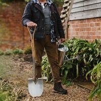 Grävspade och vattenkanna i trädgården