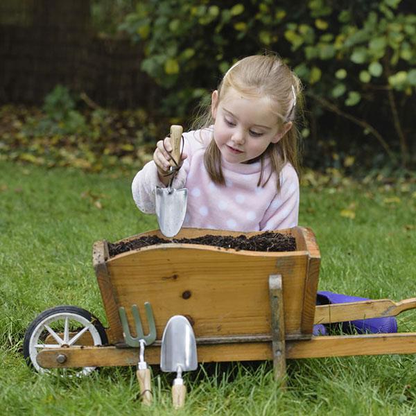Barn med trädgårdsredskap i barnstorlek