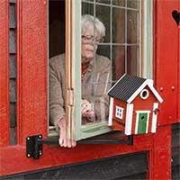 Svängarm till fågelbord/holk visas vid fönster.